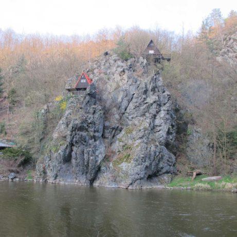 Malownicze chatki nad Wełtawą zwisające naskale nad taflą wody.