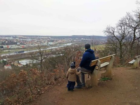 Widok na Pragę. Mężczyzna z dzieckiem patrzą przed siebie.